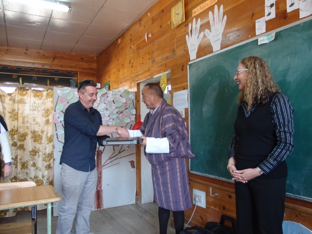 Stewart Duff and Professor Sue Carrington handing over a laptop to a Bhutanese teacher