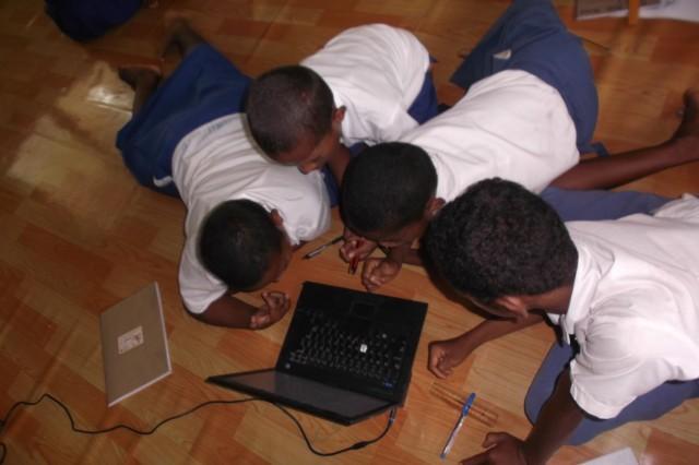 Children using  laptops for school work